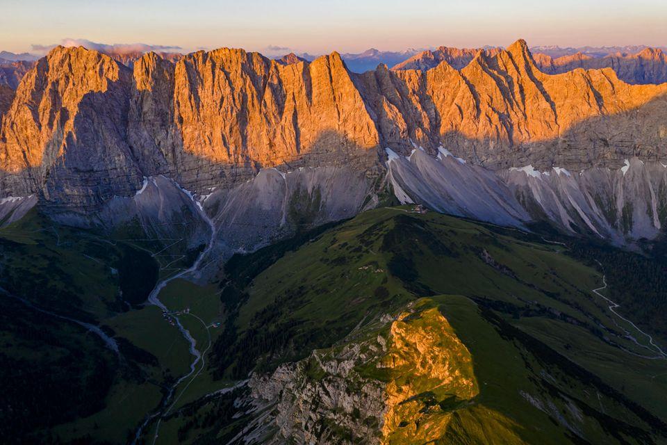 Die Szenerie erinnert an Patagonien. Markante Felsklippen strahlen golden im Abendlicht, tief unten liegen die eingeschnittenen Täler bereits im Dunkeln