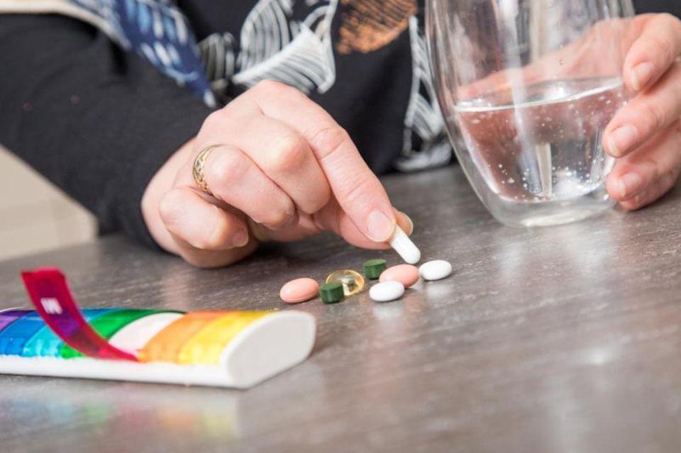 Eine Frau hat vieel Pillen auf dem Tisch liegen und will sie einnehmen.