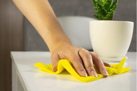 Frau putzt einen Tisch ab