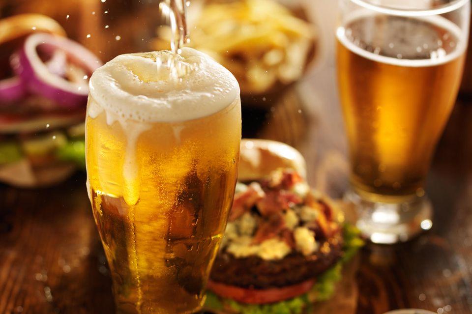 Volles Bierglas auf Esstisch mit Fast Food