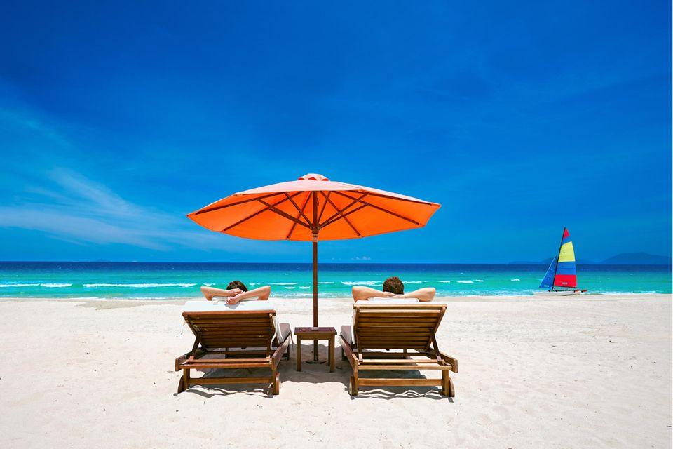 Ein Paar sonnt sich auf Liegen am Strand mit Blick aufs Meer