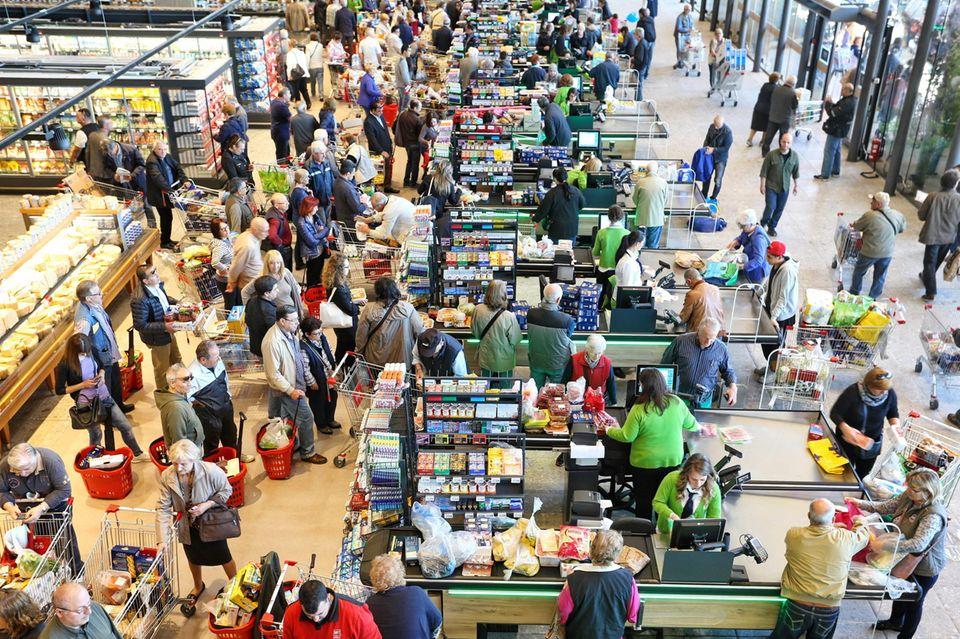 Wartende Menschen an der Supermarktkasse