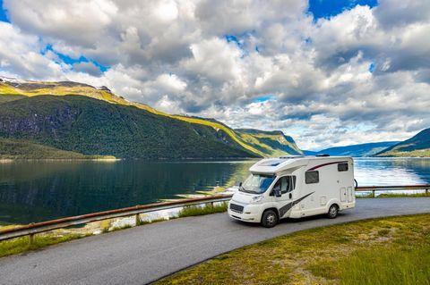 Wohnmobil fährt auf einer Straße mit See im Hintergrund
