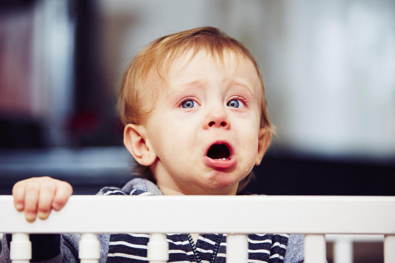 Kleiner Junge weint im Gitterbett