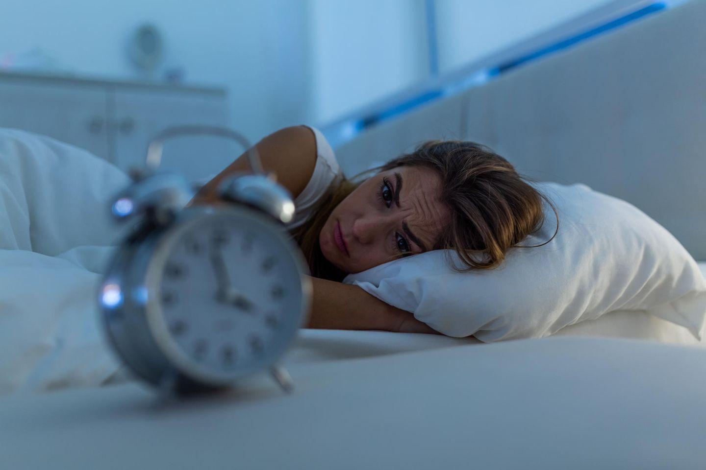 Frau liegt im Bett und kann nicht schlafen