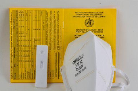 Impfausweis, Test und FFP2-Maske leigen nebeneinander