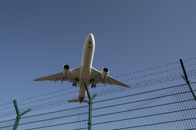 Flugzeug fliegt über einen Zaun