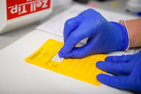 Aufkleber für eine Impfung wird in den gelben Impfpass geklebt