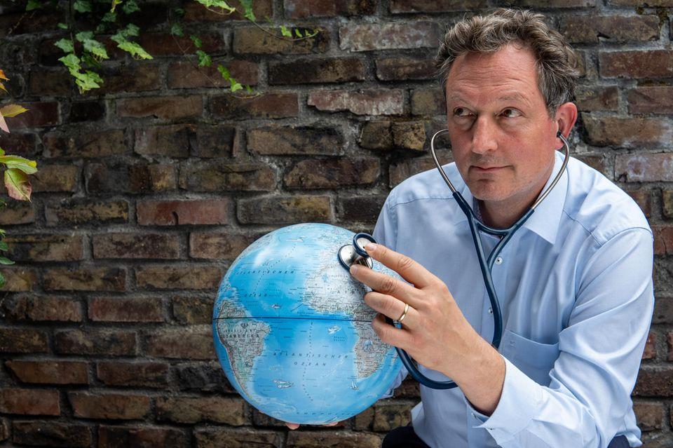 Eckart von Hirschhausen hört einen Globus ab