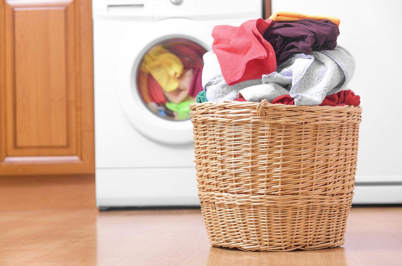 Wäschekorb steht vor einer Waschmaschine