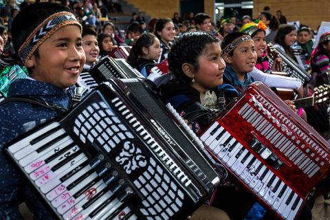 The annual music concert given by the one thousand one hundred and twenty children who participate in the Papageno music school programme of music education given to rural primary school kids in the Araucanía region of Chile. Seen here a group of native...