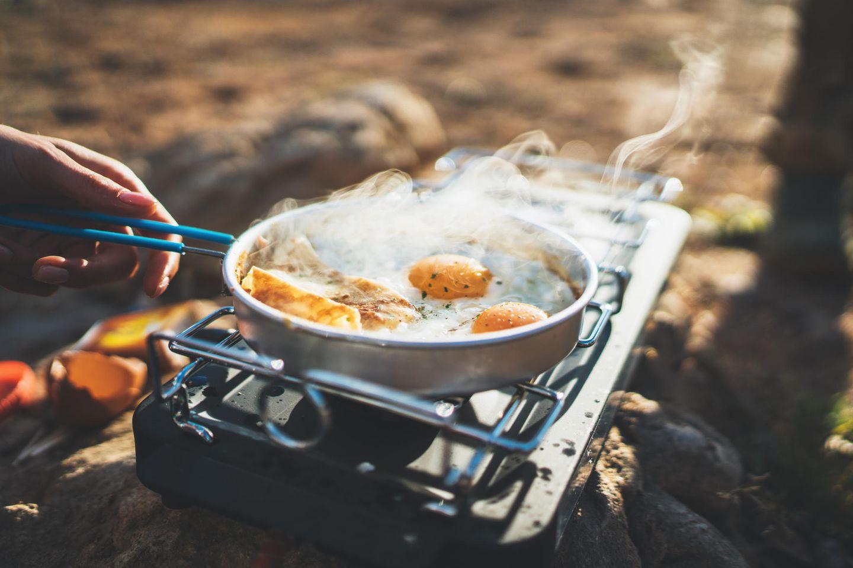 Person brät Eier auf einem Campingkocher