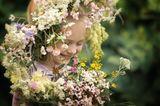 Glückliches Mädchen mit einem Blumenkranz