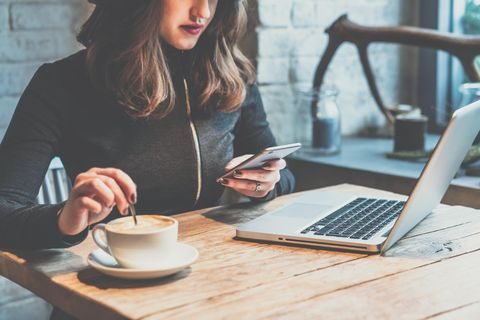Frau sitzt beim Arbeiten am Laptop an einem Holztisch, trinkt Kaffee und benutzt ein Smartphone