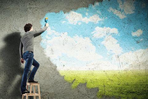 Mann auf einer Leiter malt ein Wandbild