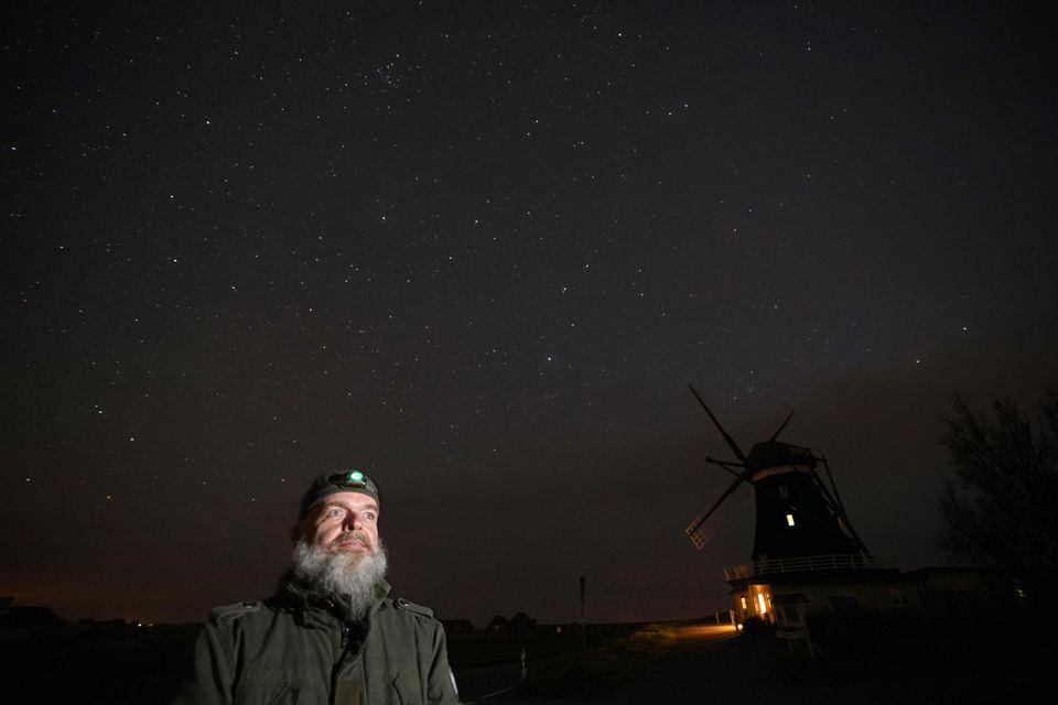 Oliver Jedath von der Projektgruppe Sterneninsel Pellworm steht in der Nacht mit einer Stirnlampe an der Nordermühle auf der Insel Pellworm