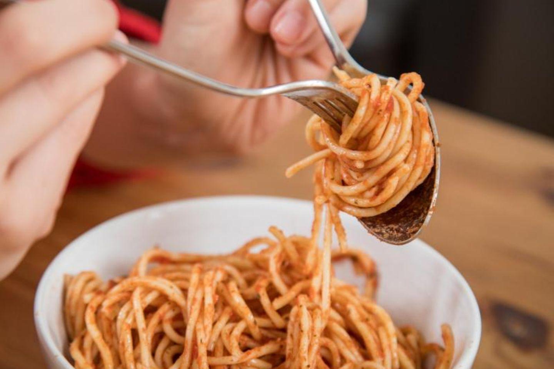 Spaghetti werden auf eine Gabel gerollt
