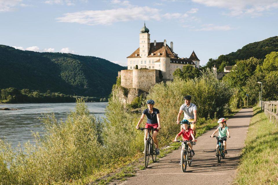 Eine Familie radelt auf dem Donauradweg an Schloss Schönbiel vorbei