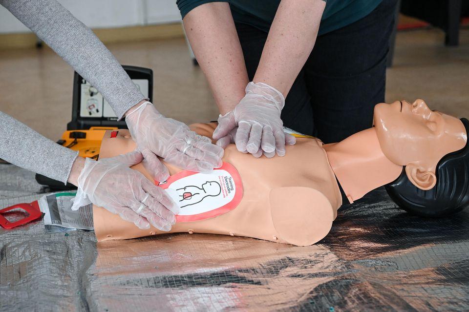 Ausbilderinnen vom Arbeiter-Samariter-Bund (ASB) demonstrieren an einer Reanimationspuppe in einem Ersthelferkurs dieWiederbelebungmit Einsatz eines Defibrillators
