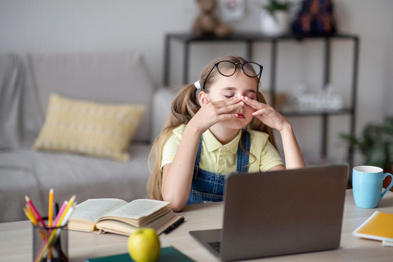 Mädchen sitzt vor dem PC und reibt sich die Augen