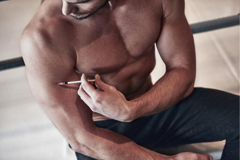 Bodybuilder spritzt sich Stereoide in den Arm
