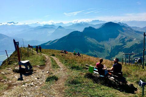 Touristen sitzen am Moléson-sur-Gruyères
