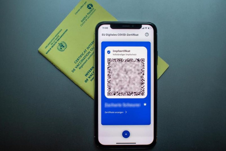 Impfpass un digitaler Impfpass auf dem Handy liegen auf dem Tisch