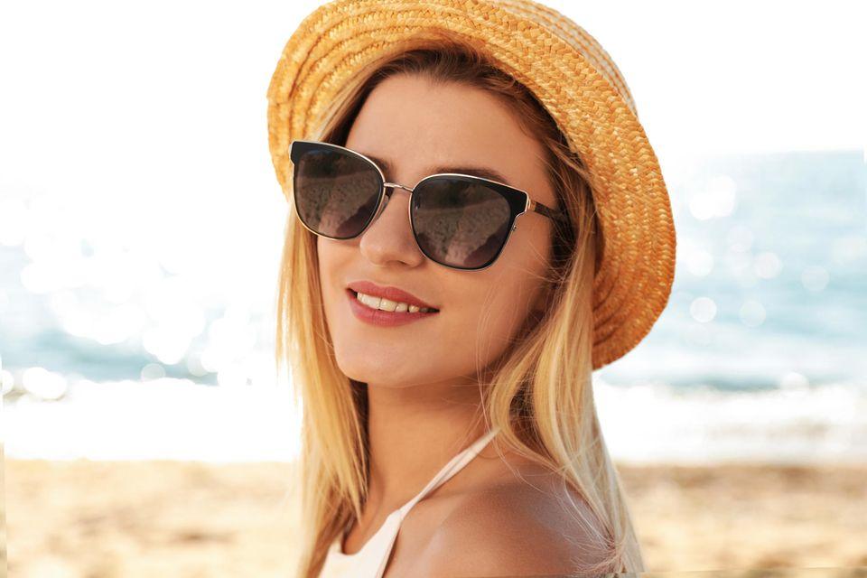 Frau mit Sonnenbrille am Strand lacht in die Kamera