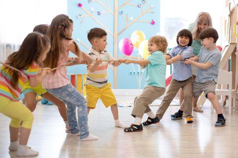 Kinder spielen Tauziehen in der Kita