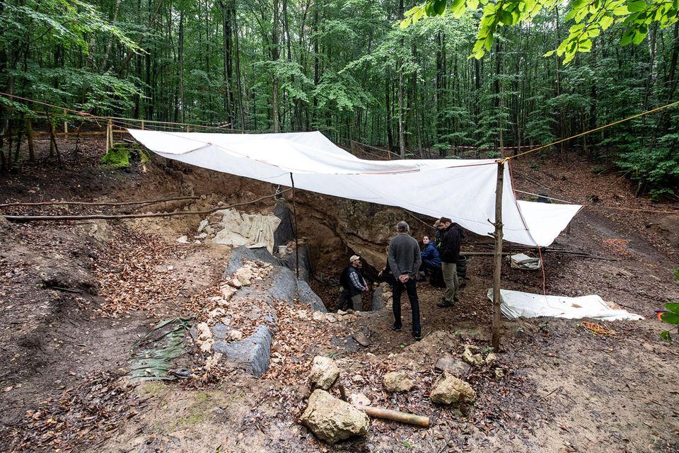 Archäologen stehen unter einer Plane bei den Ausgrabungen an der Einhornhöhle