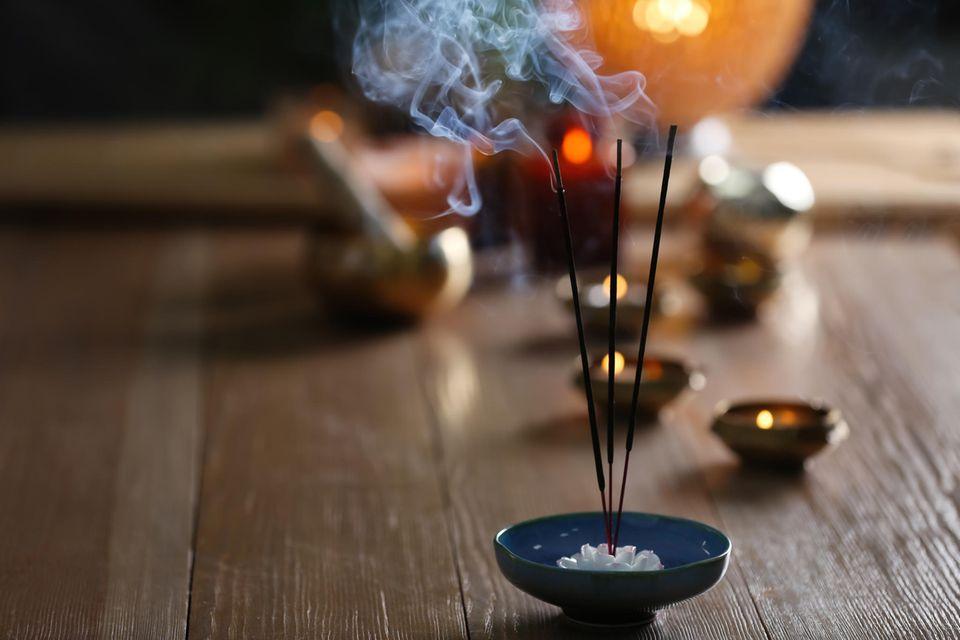 Rauchende Räucherstäbchen auf einem Holztisch mit Kerzen