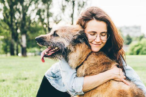 Lächelnde Frau umarmt ihren Hund