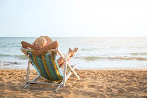 Frau mit Sonnenhut entspannt im Liegenstuhl am Strand