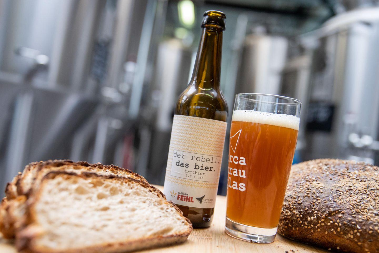 Eine Flasche Brotbier steht neben einem gefüllten Glas zwischen Brotscheiben in der Craftbier-Brauerei Orca Brau. Die Brauerei braut Bier aus Brot, welches sonst in der Mülltonne landen würde. Etwa 30 Prozent des Braumalzes werden mit Brot ersetzt, welches in den 35 Filialen der Bäckerei Feihl in der Region nicht verkauft wurde