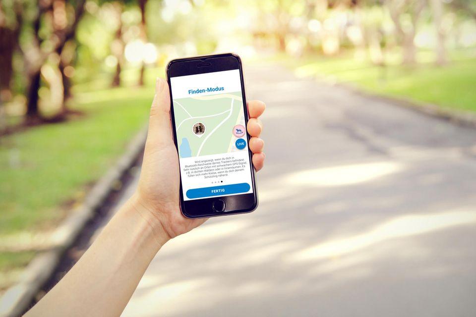 """Frau hält ihr Smartphone mit der App """"Tractive"""" draußen in der Hand"""