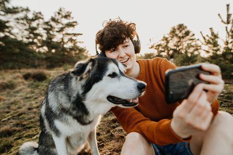 Junge Frau und Hund sitzen in der Natur und schauen auf ein Smartphone