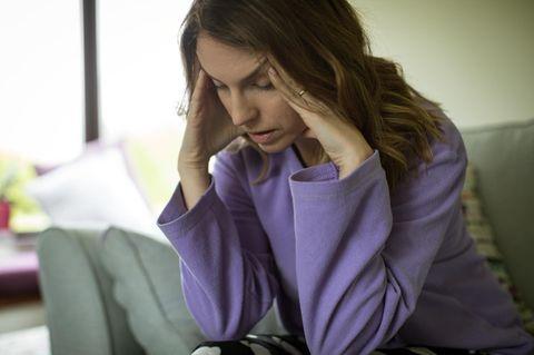 Frau greift sich an den Kopf, weil sie Kopfschmerzen hat