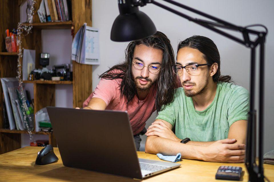Junge Zwillingsbrüder schauen gemeinsam auf den Bildschirm eines Laptops