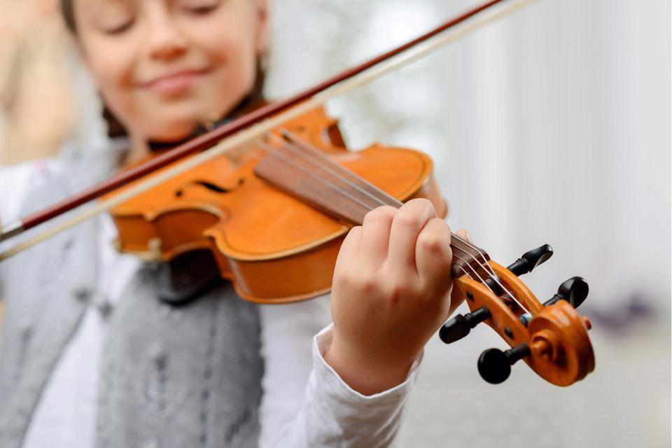 Eine junge Frau spielt lächelnd Geige