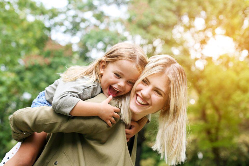 Lachende Mutter hält Tochter auf dem Rücken