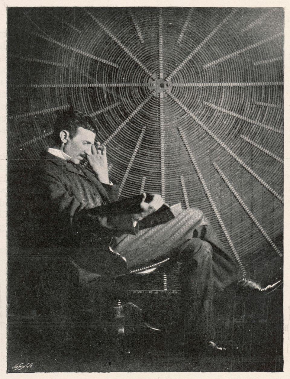 Nikola Tesla sitzt lesend in seinem Labor