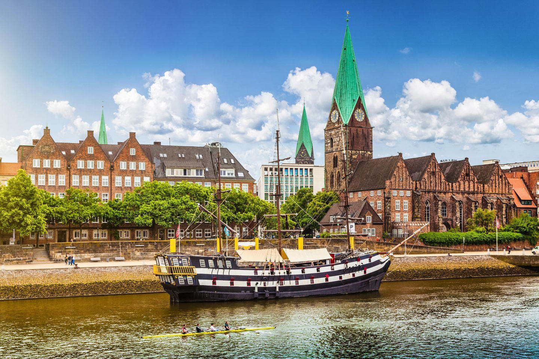 Stadtpanorama von Bremen mit altem Segelschiff auf der Weser