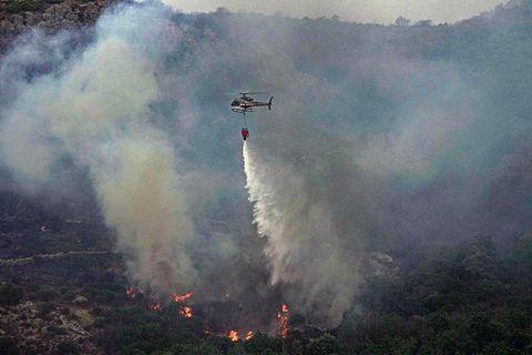 Ein Hubschrauber wirft über einem Waldgebiet in Cugliari Wasser ab, um Flammen zu löschen