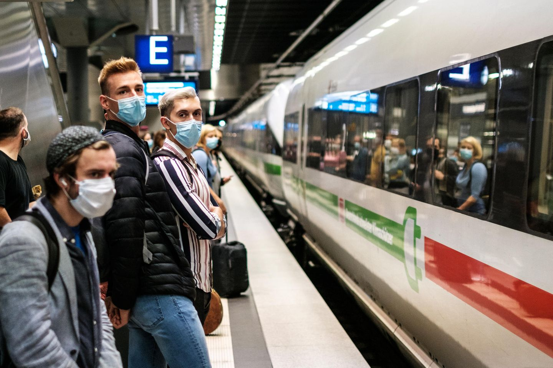 Menschen tragen Masken und stehen am Bahnsteig