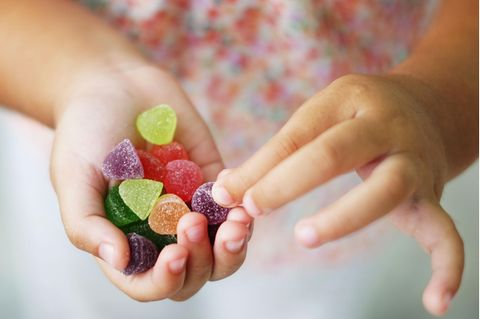 Kleinkind hält gezuckerte Geleebonbons in der Hand