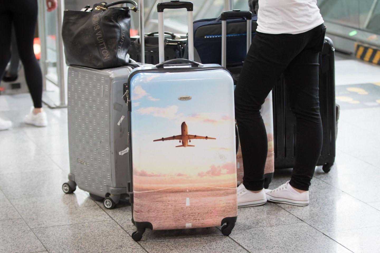 Urlauberinnne und Urlauber stehen mit dem Koffer am Flughafen