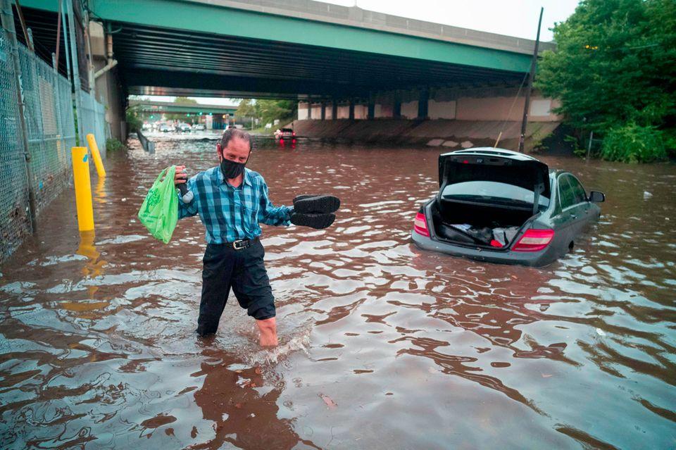 USA, Newark: Ein Mann watet durch das Hochwasser einer überschwemmten Straße während einer Sturzflut in diesem Gebiet.