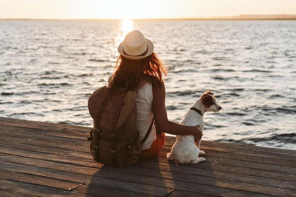 Frau sitzt mit ihrem Hund euf einem Steg und schaut in die Ferne