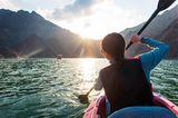 Frau fährt mit dem Kayak über den großen Hatta-Stausee im Abendlicht
