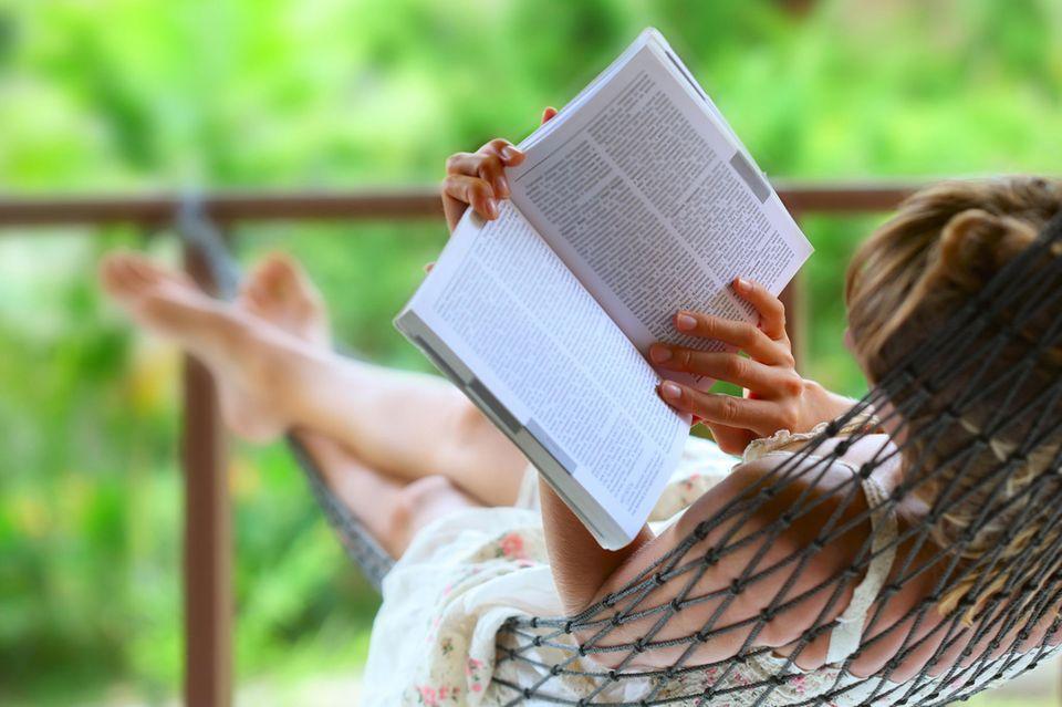 Frau liest in einer Hängematte ein Buch